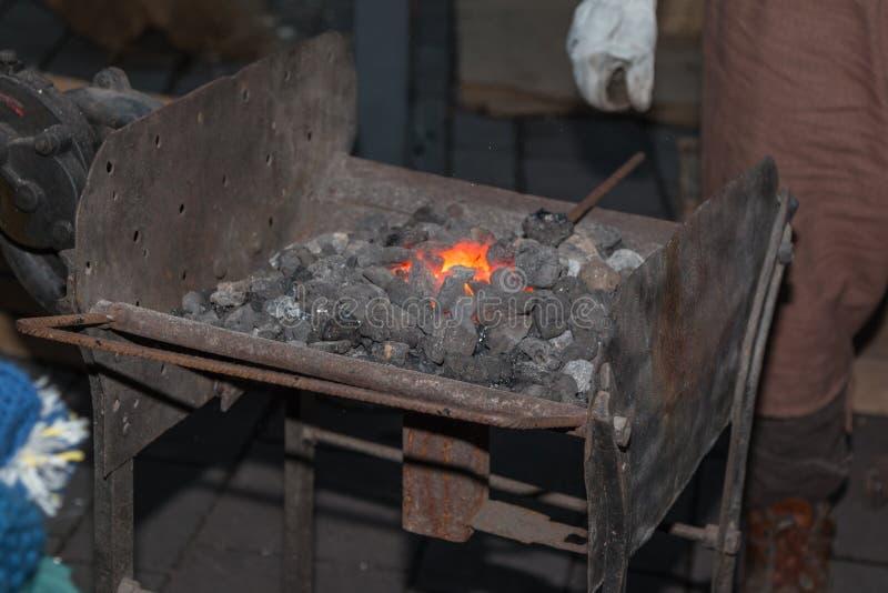 Un four de pièce forgéee : Forgeron Working Iron et charbon de bois incandescent images libres de droits