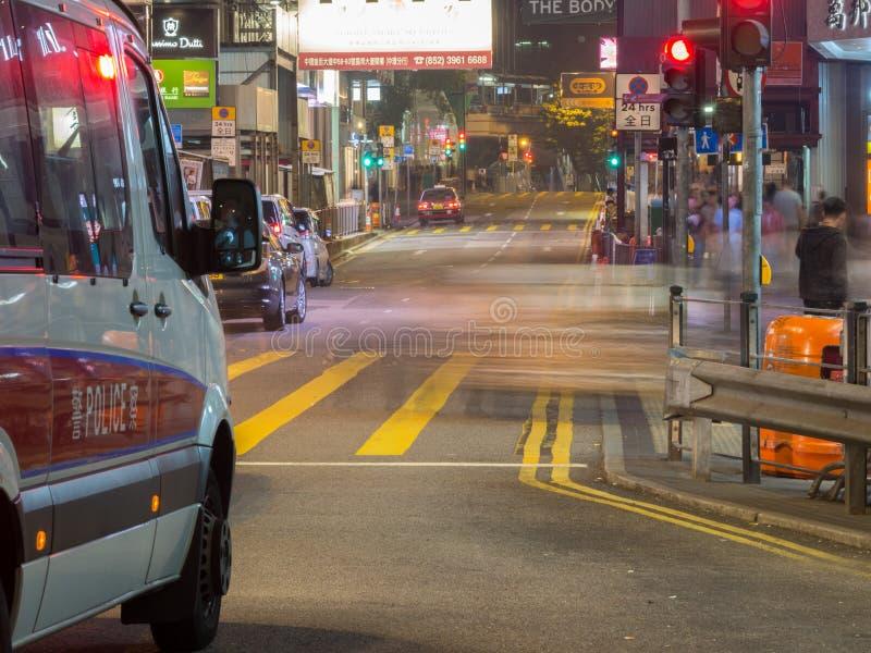 Un fourgon de la police de Hong Kong, se tenant devant la lumière rouge au central de la route de la Reine images stock