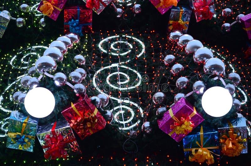 Un fragment d'un arbre de Noël énorme avec beaucoup d'ornements, de boîte-cadeau et de lampes lumineuses Photo d'une fin décorée  photo stock