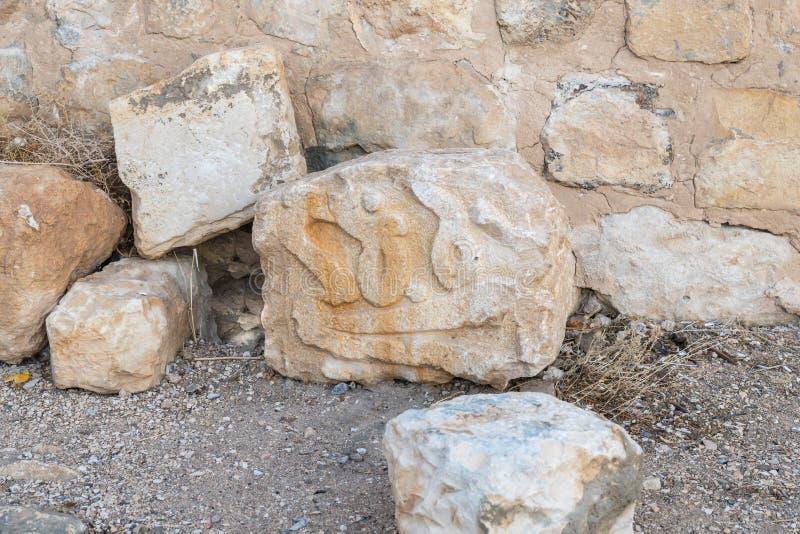 Un fragment d'un mur avec un modèle découpé là-dessus se trouve au sol près du mur de la forteresse médiévale Ash Shubak, se tena photographie stock