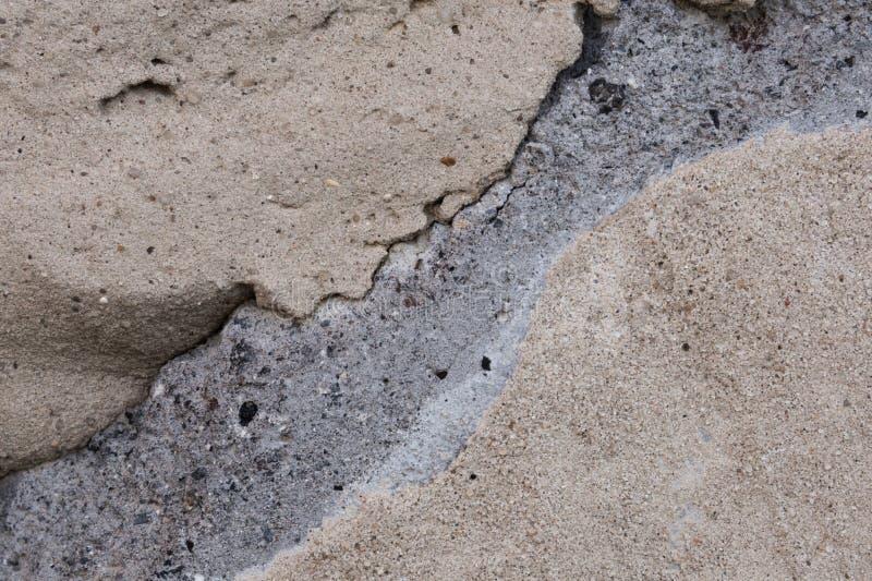 Un fragment d'un mur des blocs de béton, le long desquels les fissures sont allées photos libres de droits