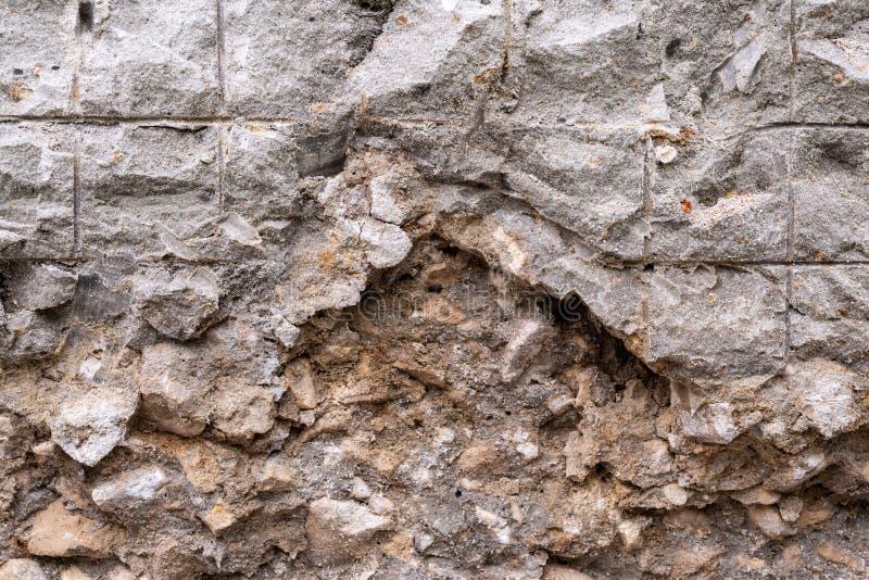 Un fragment d'un mur des blocs de béton, le long desquels les fissures sont allées image stock