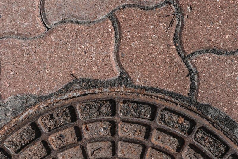 Un fragment du couvercle du puits et du trottoir abr?gez le fond Orientation molle image stock