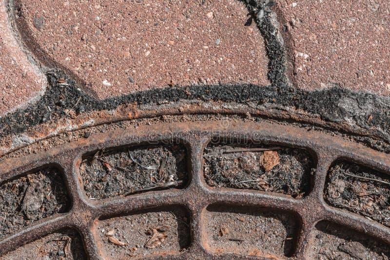 Un fragment du couvercle du puits et du trottoir abr?gez le fond Orientation molle images stock