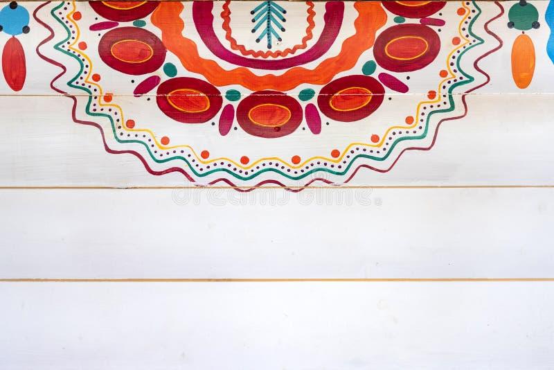 Un fragmento colorido del modelo ruso en el estilo de Dymkovo en la pared de madera pintada en blanco imagen de archivo libre de regalías
