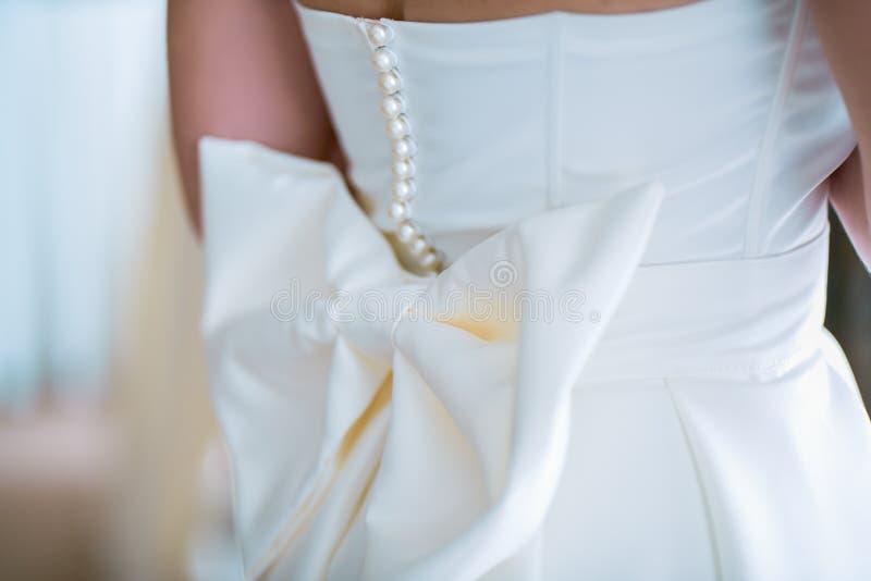 Un fragmento de la parte posterior de la novia, arco grande del vestido de boda foto con un tinte arenoso imágenes de archivo libres de regalías