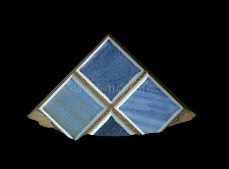 Un fragmento de la textura El acabamiento de cerámica azul teja el bloque aislado decorativo en un fondo negro el fragmento aisla foto de archivo
