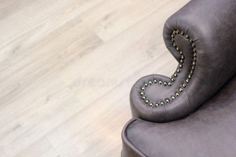 Un fragmento de los apoyabrazos de una silla de cuero clásica con la decoración Industria de los muebles Textura del fondo con el imágenes de archivo libres de regalías