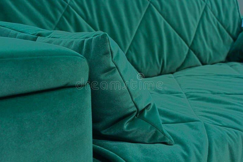 Un fragmento de un sofá verde del terciopelo fotografía de archivo