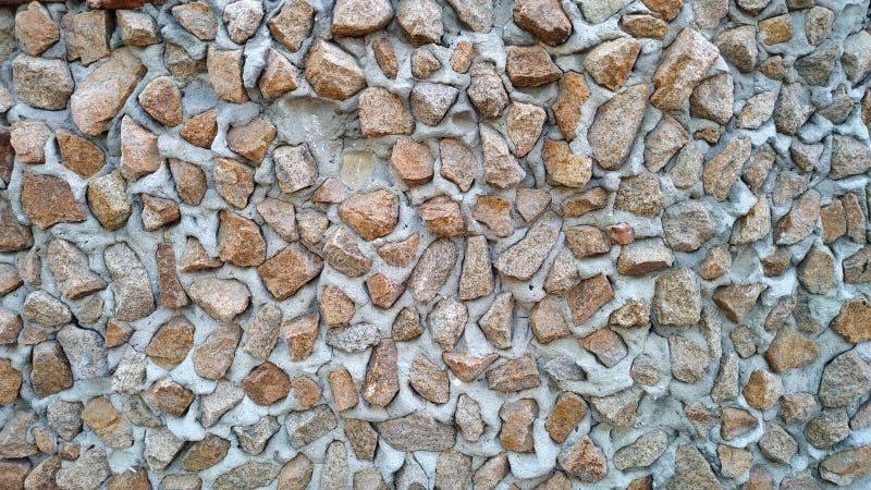 Un fragmento de una cerca de piedras y de ligamentos del cemento Fondo, textura Primer fotografía de archivo libre de regalías