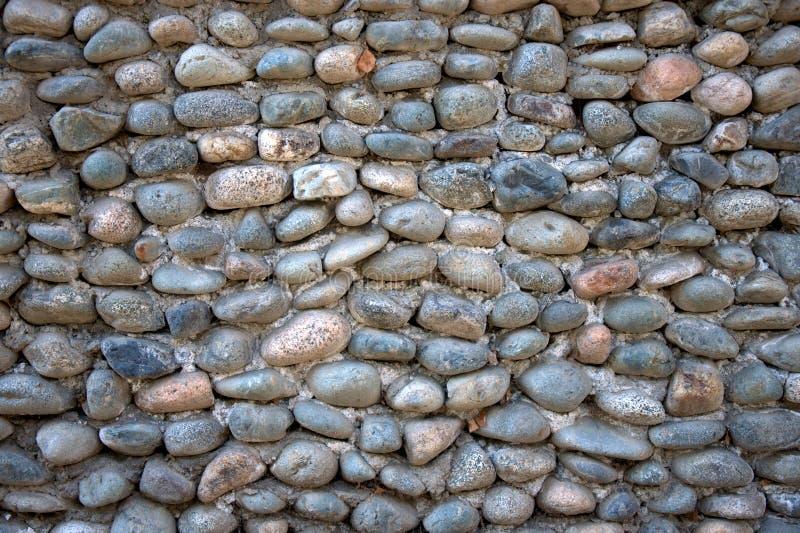 Un fragmento de una cerca de piedras y de ligamentos redondos del cemento fotografía de archivo