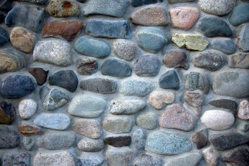 Un fragmento de una cerca de piedras y de ligamentos redondos del cemento Fondo, textura Paisaje imágenes de archivo libres de regalías