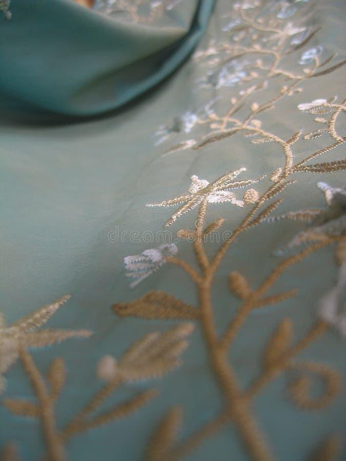 Un frammento del tessuto ricamato del turchese fotografia stock
