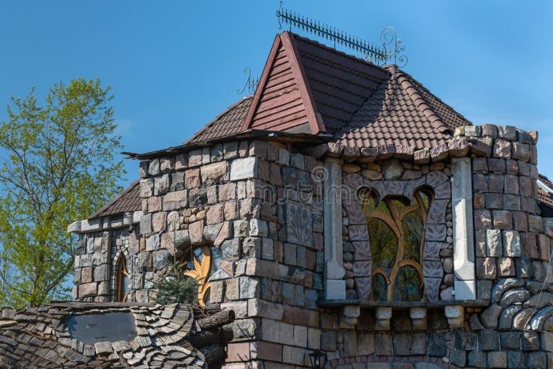 Un frammento di bella casa della pietra ruvida contro il cielo blu Riflessione dell'albero nella finestra immagine stock libera da diritti