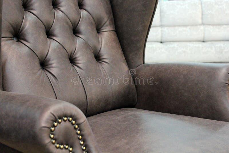 Un frammento di una sedia di cuoio classica Primo piano di struttura di cuoio elegante con i bottoni Frammento di una sedia class fotografia stock libera da diritti