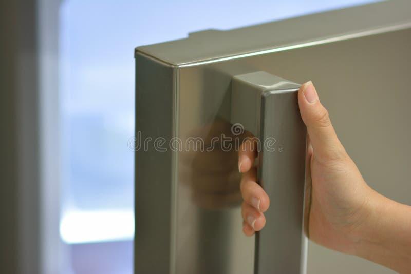 Un frigorifero di apertura della mano fotografia stock