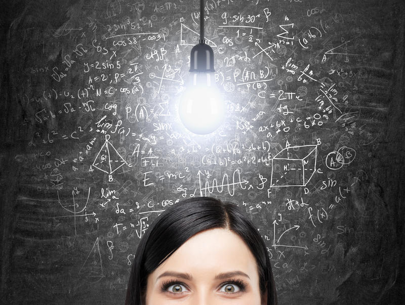 Un front de la femme de brune qui pense à la solution du problème de maths compliqué Les formules de maths sont sur le tableau no image libre de droits