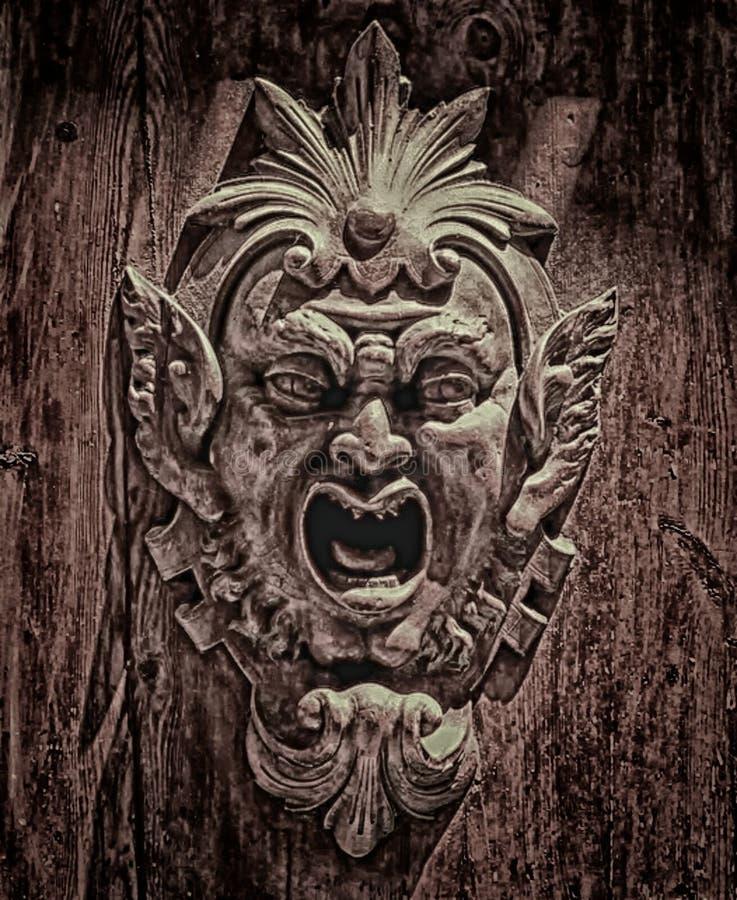 Un fronte di legno scolpito complesso di un diavolo monsterous, fotografia stock