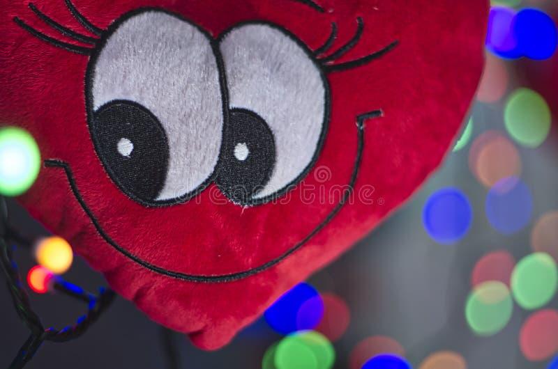 Un fronte sorridente in un cuore della peluche immagini stock