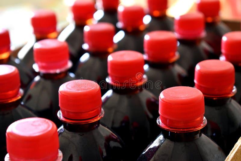 Un fruit rouge foncé réduit en sirop dans des bouteilles en plastique avec les couvercles rouges sont prêt pour la distribution image libre de droits