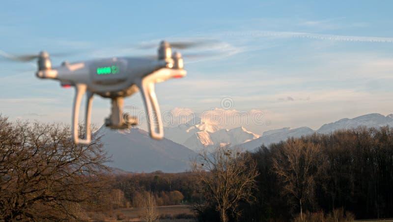 Un fuco si libra in volo davanti alle montagne delle alpi in Francia immagine stock