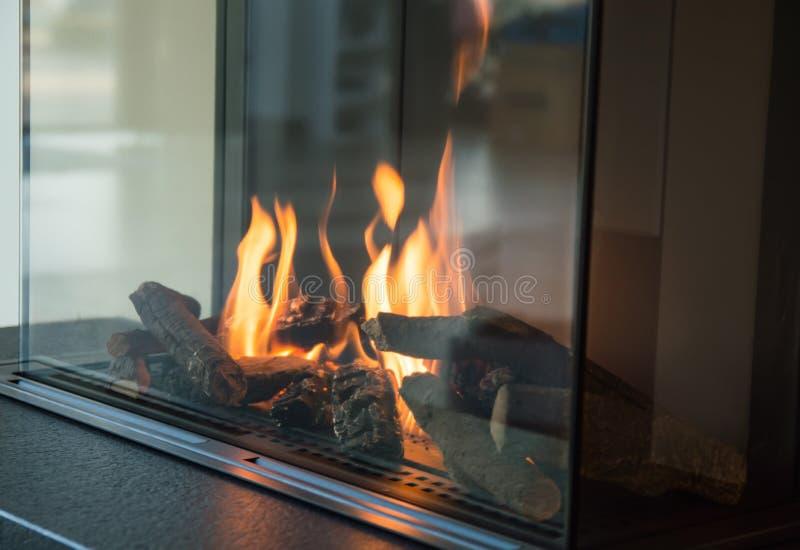 Un fuego quema en una chimenea de cristal, irradia calor imagenes de archivo