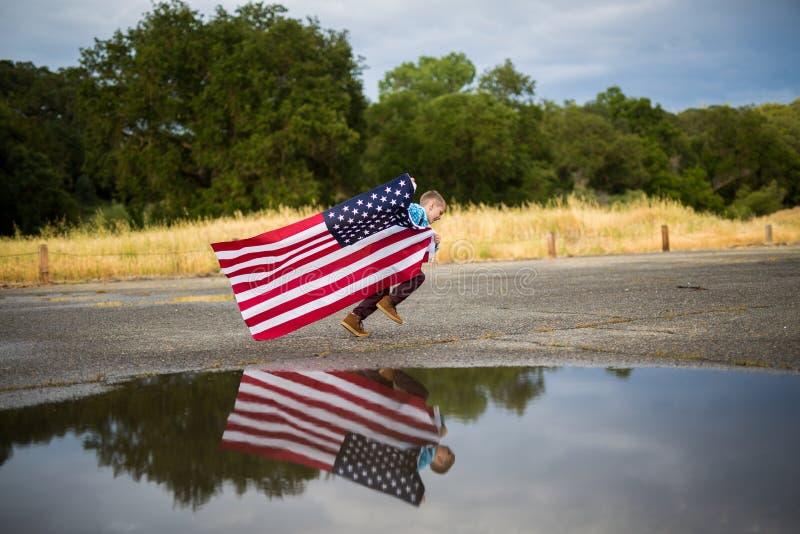 Un funcionamiento joven del muchacho mientras que sostiene la bandera americana que muestra el patriotismo para su propio país, u imágenes de archivo libres de regalías