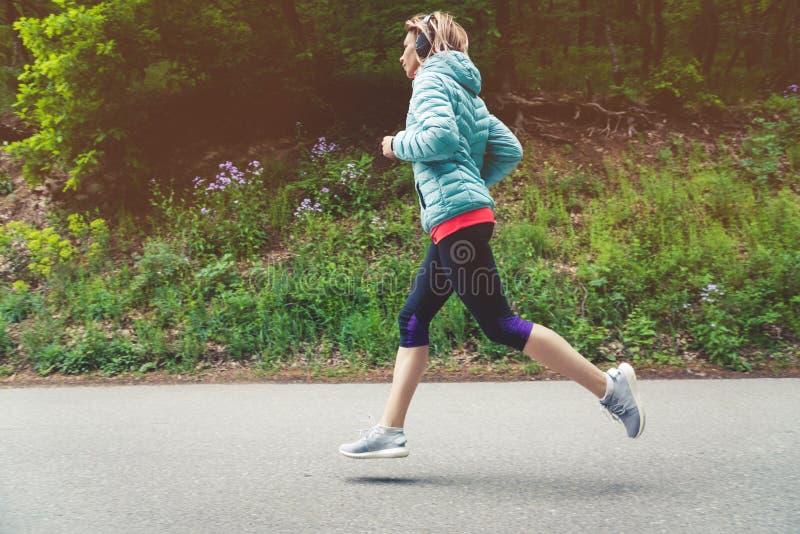 Un funcionamiento rubio joven de la mujer está practicando al aire libre en un parque de la montaña de la ciudad en los rayos cal imagen de archivo