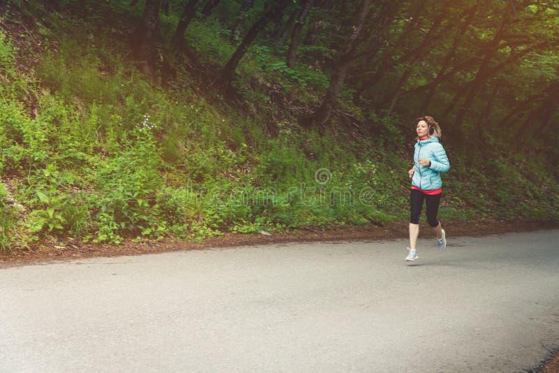 Un funcionamiento rubio joven de la mujer está practicando al aire libre en un parque de la montaña de la ciudad en los rayos cal fotos de archivo libres de regalías
