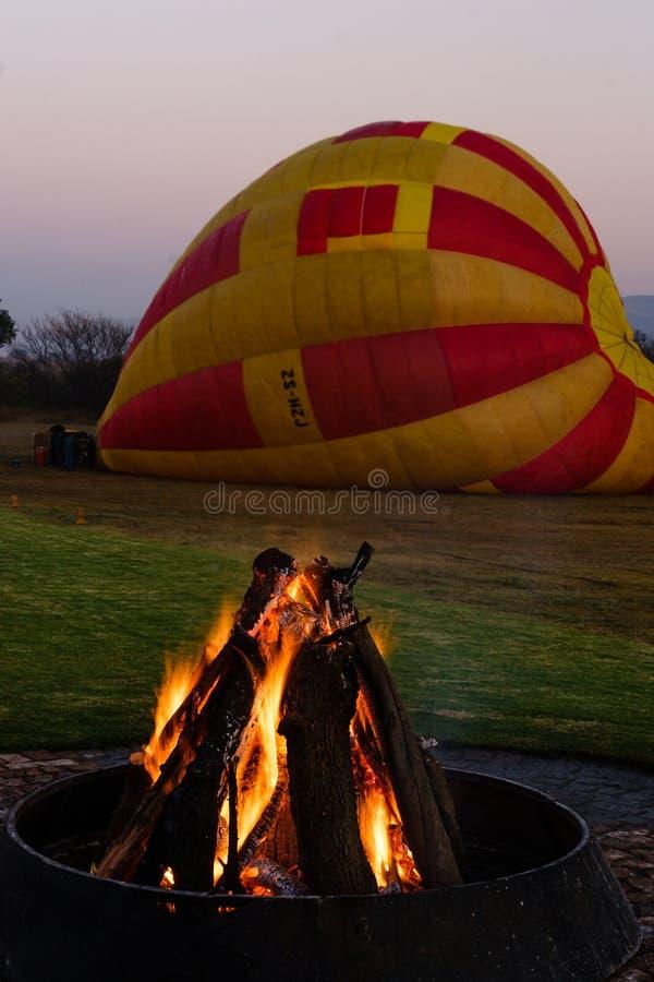 Un fuoco brucia nel primo mattino prima di un volo della mongolfiera fotografie stock