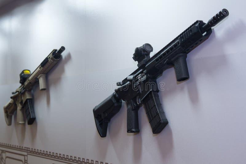 Un fusil d'assaut accroche sur un mur dans une armurerie photo libre de droits