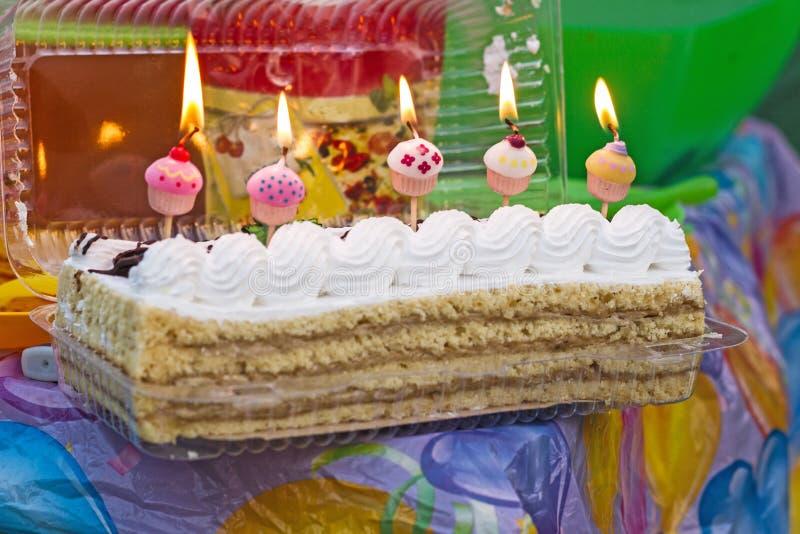 Un gâteau de fête de banane avec de la crème et des bougies cinq cloches pour un anniversaire sur un pique-nique sur un fond de f photographie stock