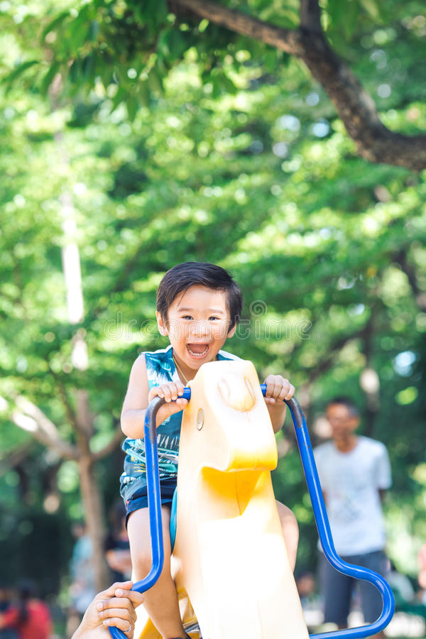 Un garçon asiatique joue un cheval de basculage dans un terrain de jeu extérieur photos stock