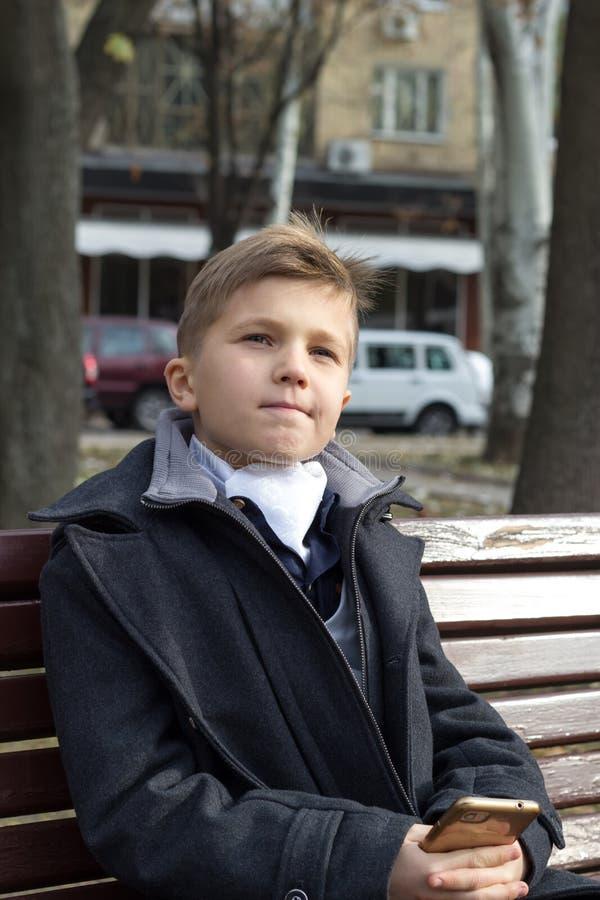 Un garçon assis sur un banc dans un parc habillé en affaires avec un regard attentif et un léger sourire Réflexion sur son photos stock