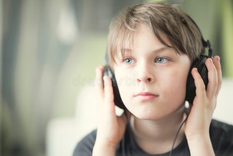 Un garçon avec des écouteurs images stock