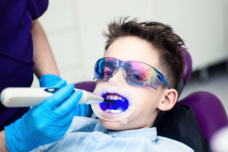 Un garçon avec des lunettes dans la chaise dentaire La bouche a dirigé la lampe de lightpolymerization avec la lumière bleue pour images libres de droits