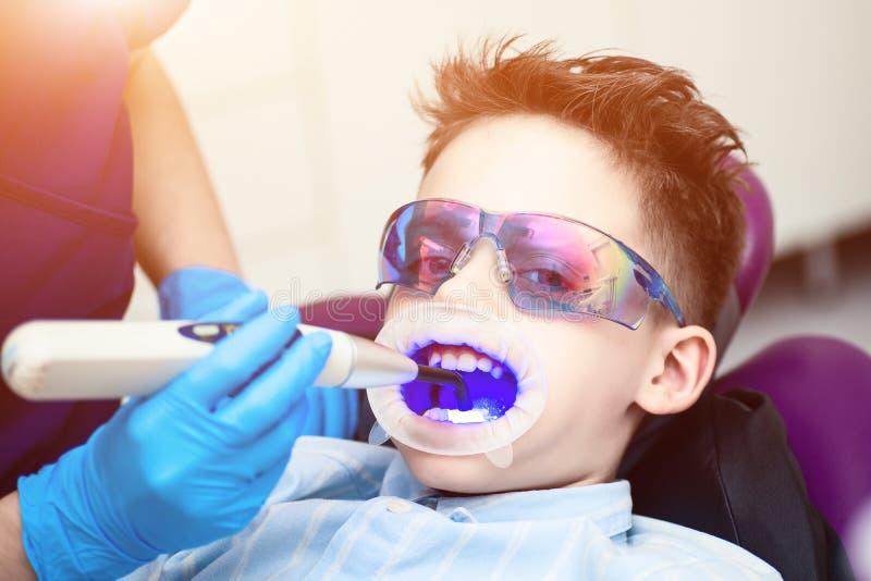 Un garçon avec des lunettes dans la chaise dentaire La bouche a dirigé la lampe de lightpolymerization avec la lumière bleue pour photos libres de droits