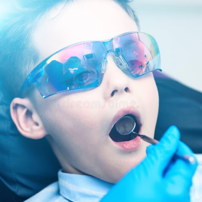 Un garçon avec des lunettes dans la chaise dentaire Le docteur examine la cavité buccale avec un miroir dentaire spécial photographie stock