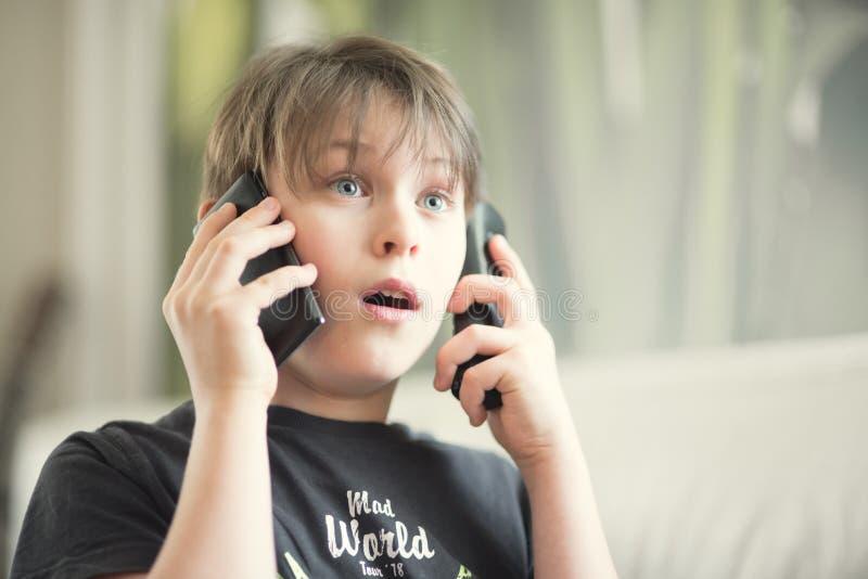 Un garçon avec des téléphones image stock