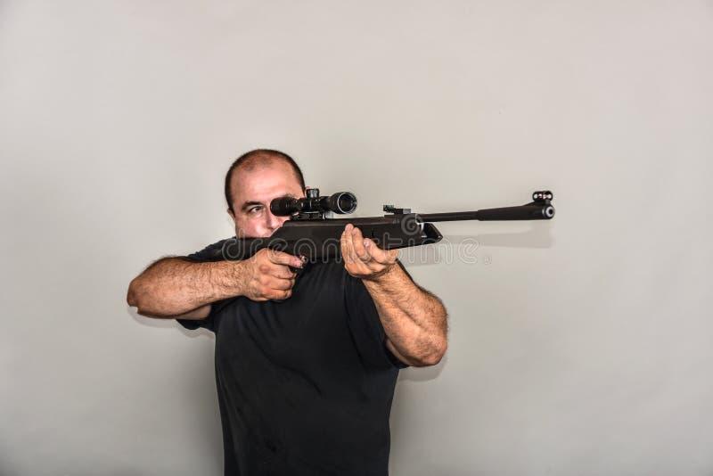 Un garçon avec un fusil à air comprimé examine un appareil optique de visée photographie stock libre de droits