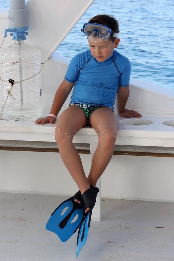 Un garçon avec les nageoires et le masque à nager photos stock