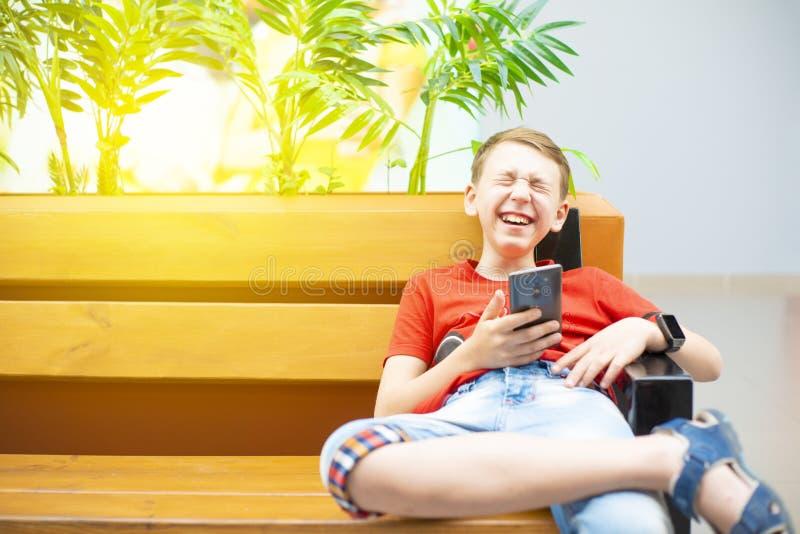 Un garçon avec un smartphone et une horloge intelligente s'assied sur un banc et examine le téléphone et rit dur Photo avec la te photographie stock