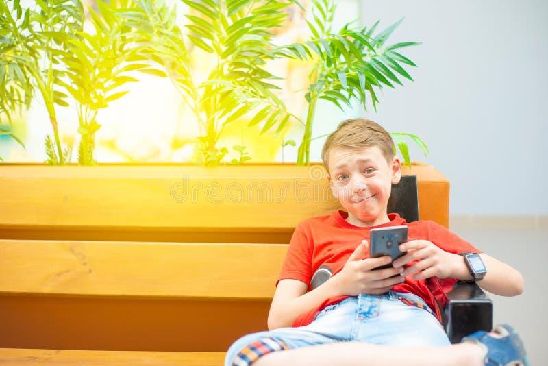 Un garçon avec un smartphone et une horloge intelligente s'assied sur un banc et examine le téléphone et rit dur Photo avec la te photos libres de droits