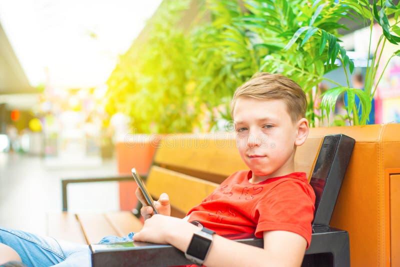 Un garçon avec un smartphone et une horloge intelligente s'assied sur un banc souriant et regardant l'appareil-photo Photo avec l photographie stock