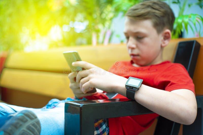 Un garçon avec un smartphone s'assied sur un banc et écrit et lit un message Photo avec la teinture image libre de droits
