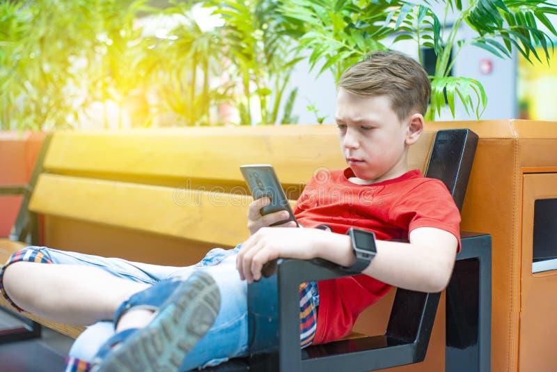 Un garçon avec un smartphone s'assied sur un banc et écrit et lit un message Photo avec la teinture photos stock