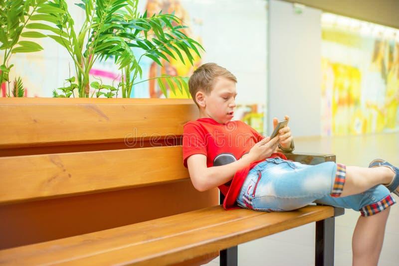 Un garçon avec un smartphone s'assied sur un banc et écrit et lit un message Photo avec la teinture photographie stock libre de droits