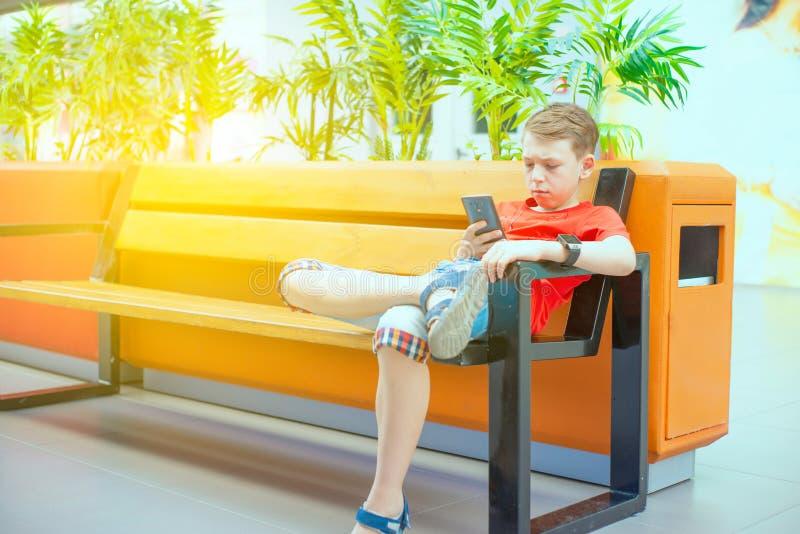 Un garçon avec un smartphone s'assied sur un banc et écrit et lit un message Photo avec la teinture photos libres de droits
