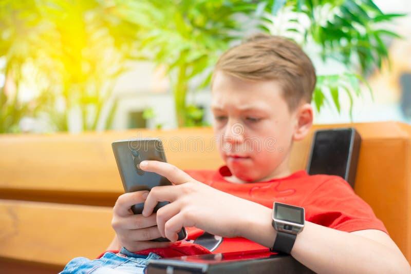 Un garçon avec un smartphone s'assied sur un banc et écrit et lit un message Photo avec la teinture image stock