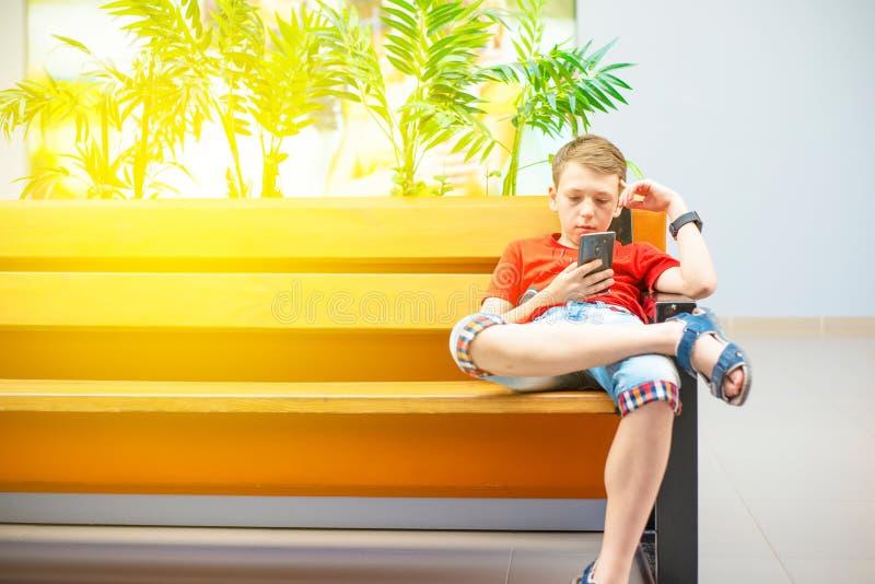 Un garçon avec un smartphone s'assied sur un banc et écrit et lit un message Photo avec la teinture images stock